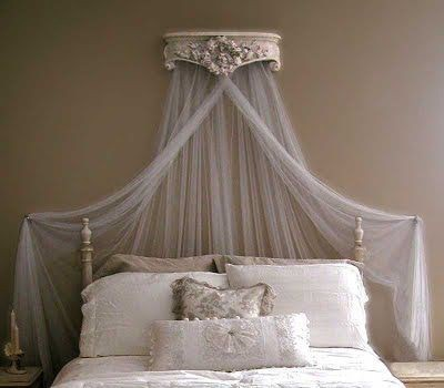 A fancy small bed with ornate pillows