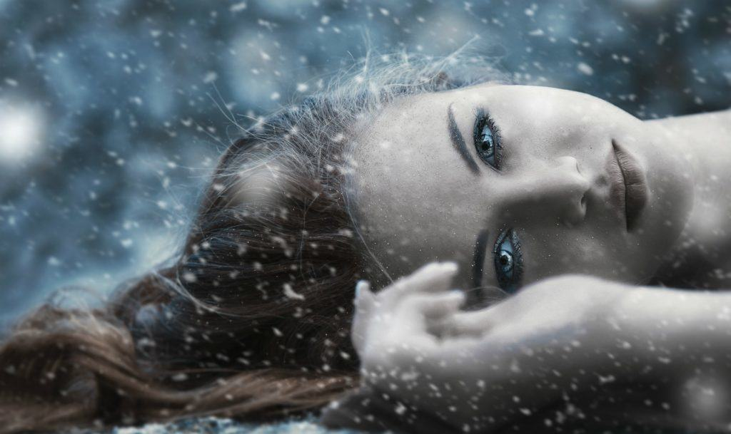 A young woman with captivating eyes lying on the ground, looking at the viewer
