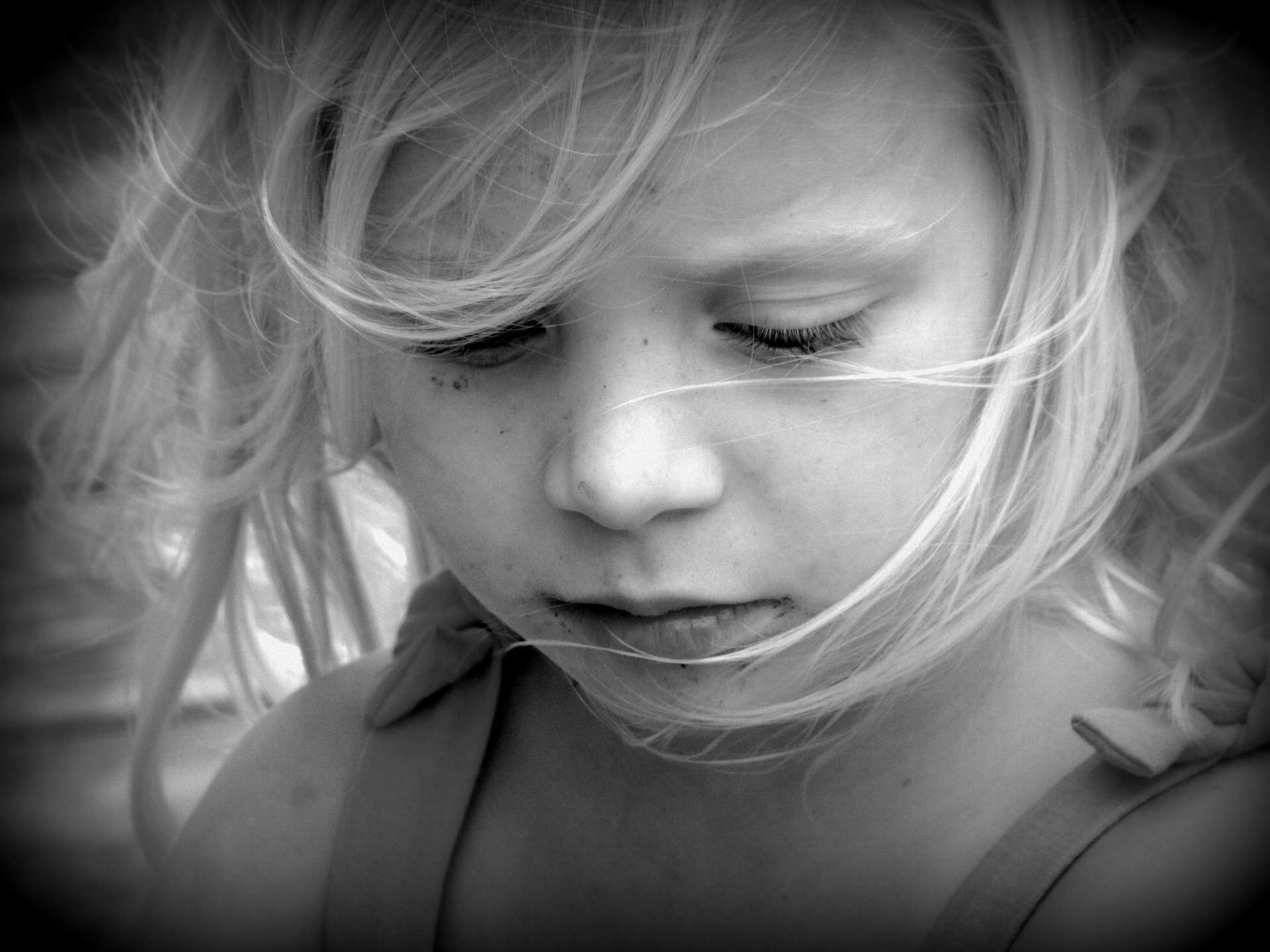 Little blond girl looking down