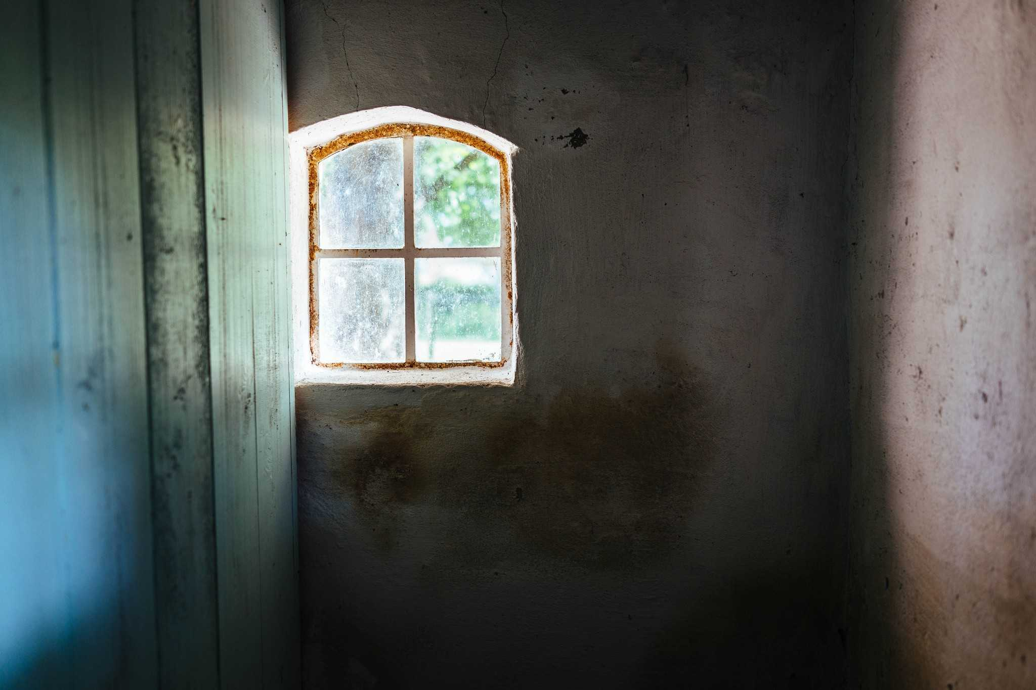 A window inside a bland home letting light through